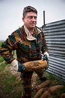 Dirk Van Parijs, team leader with the Belgian Unexploded Ordnance Diposal Group, removes an unexploded WWI shell that has been left in a roadside telegraph pole by farmer. It could contain high explosive or mustard or phosgene poison gas.