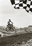 USA, Tennessee, motocross winner jumping across the finish line (B&W)