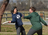 STAFF PHOTO BEN GOFF  @NWABenGoff -- 12/29/14 Orion O'Connor, 13, left, tries to pass the disc as opponent Sylas Hackett, 17, both of Bentonville, guards while playing in a pick up Ultimate game at Phillips Park in Bentonville on Monday Dec. 29, 2014.