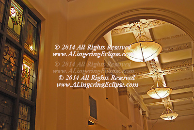 Stained glass window panels, back-lit, antique light fixtures, arched entryway, pillars/columns and ceiling ornamentation in an historic New York City building, The Gregorian Hotel