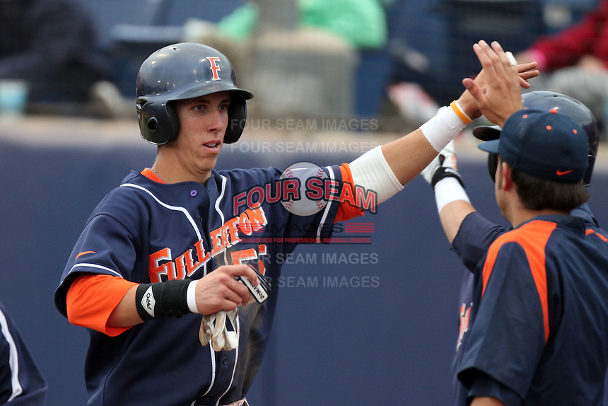 Michael Lorenzen #55 of the Cal. St. Fullerton Titans is greeted by teammates after scoring against the Cal. St. Long Beach 49'ers at Goodwin Field in Fullerton,California on May 14, 2011. Photo by Larry Goren/Four Seam Images