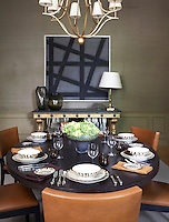 A large oval table is laid for lunch in a dining room with a duo tone abstract painting hanging on the wall