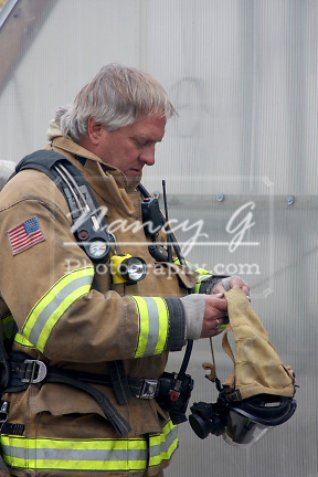 A firefighter putting on a mask