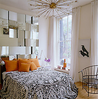 "In the bedroom the chandelier is a 1960s Lightolier and a mirror wall sculpture designed by Naeem Khan and Tom Scheerer acts as a headboard; on the adjacent wall ""Mating Crows"" by Ilse Getz"