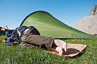 Person sleeps in sunny weather outside tent, Lofoten islands, Norway