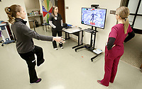 NWA Democrat-Gazette/DAVID GOTTSCHALK Sharina Cassity (from left), student of Physical Therapy, participates in a Jintronix balance and mobility exercise Tuesday, February 13, 2018, as she is observed by Kelsie Stanford, student of Physical Therapy, Heather Vaughn, physical therapist, at the University of Arkansas for Medical Sciences Northwest Outpatient Therapy Clinic in Fayetteville. The physical therapy program is new and the first cohort of 24 students is expected to graduate this May.