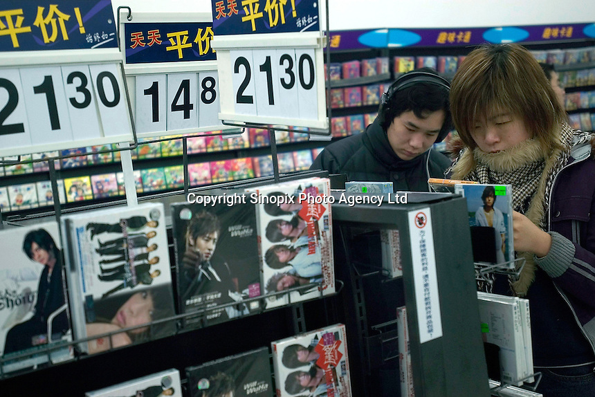 Consumers audition music CDs in a newly opened Wal-Mart Supercenter in Harbin, Heilongjiang province, China..27-DEC-04