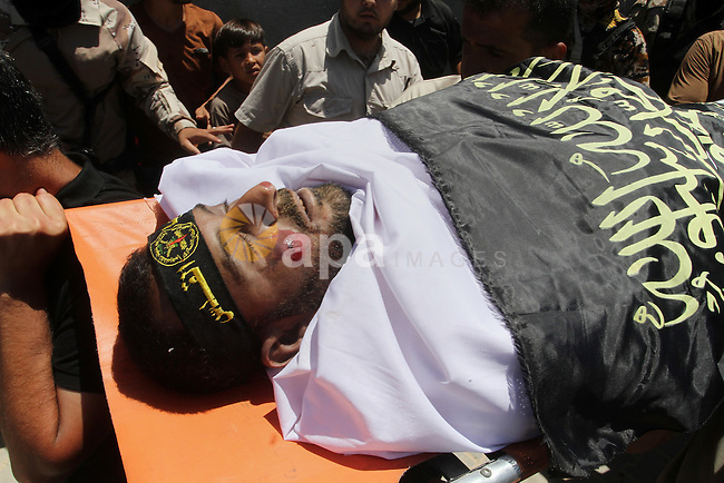 """Palestinian members of the Islamic Jihad's armed wing, the Al-Quds Brigades, carry the body of a fellow militant, Salah al-Astal, who died after a tunnel collapse in the Gaza Strip, during his funeral in Khan Younis in the southern Gaza Strip on July 19, 2016. The Al-Quds Brigades announced in a statement that Salah al-Astal had died during the """"collapse of a resistance tunnel,"""" a term used by Islamic Jihad, Hamas and other Palestinian militant factions to refer to tunnels used in the conflict with Israel. Since January 26, at least 14 Gazans have been killed in at least seven separate tunnel collapses. Photo by Abed Rahim Khatib"""
