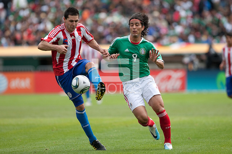 Antolin Alcaraz (5) kicks the ball ahead of Aldo De Nigris (9). Mexico defeated Paraguay 3-1 at the Oakland Coliseum in Oakland, California on March 26th, 2011.