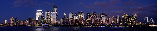 Panoramic view of the NYC Skyline at dusk with the Freedom Tower under construction dominating the skyline.