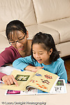 8 year old girl at home doing homework for Chinese language class working with help from mother vertical