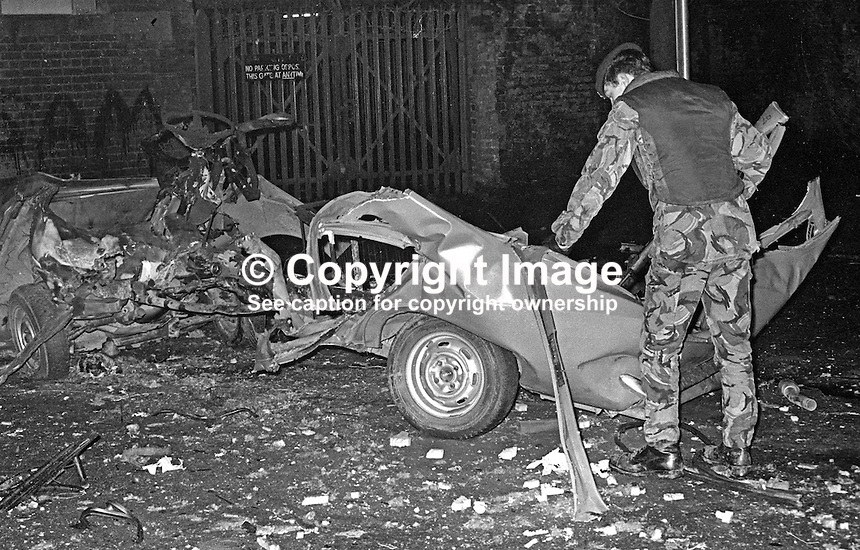 Soldier examines the mangled remains of a car in which two Provisional IRA members, Paul Fox, 20 years, and Laura Crawford, 25 years, both from Belfast, died when the bomb they were transporting exploded prematurely in King Street, close to Belfast city centre, on 1st December 1975. 19751201759.<br />