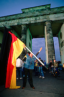 October 3, 1990. Berlin, Germany. Man with German flag standing next to Brandenburg Gate. (Photo Heimo Aga)