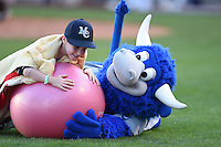 Tulsa Drillers mascot Hornsby and a young fan during an on field promotion, musical chairs, during the second game of a doubleheader against the Frisco Rough Riders on May 29, 2014 at ONEOK Field in Tulsa, Oklahoma.  Frisco defeated Tulsa 3-2.  (Mike Janes/Four Seam Images)
