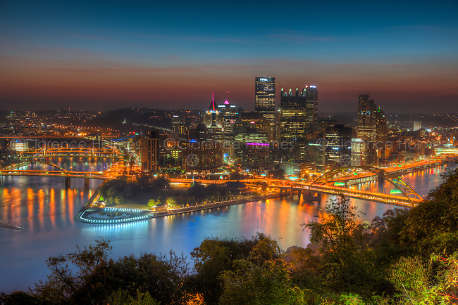 The sky glows orange during morning twilight in the last hour before sunrise over the downtown area of Pittsburgh, Pennsylvania including the skyline, bridges, and Point State Park at the confluence of the Ohio, Allegheny and Monongahela Rivers.