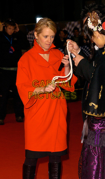 """EDITH BOWMAN.""""The Prestige"""" UK film premiere.Odeon West End cinema, Leicester Square.5th November 2006 London, England.Ref: CAN.half length red coat hand arm holding rope gold circle .www.capitalpictures.com.sales@capitalpictures.com.©Phil Loftus/Capital Pictures"""