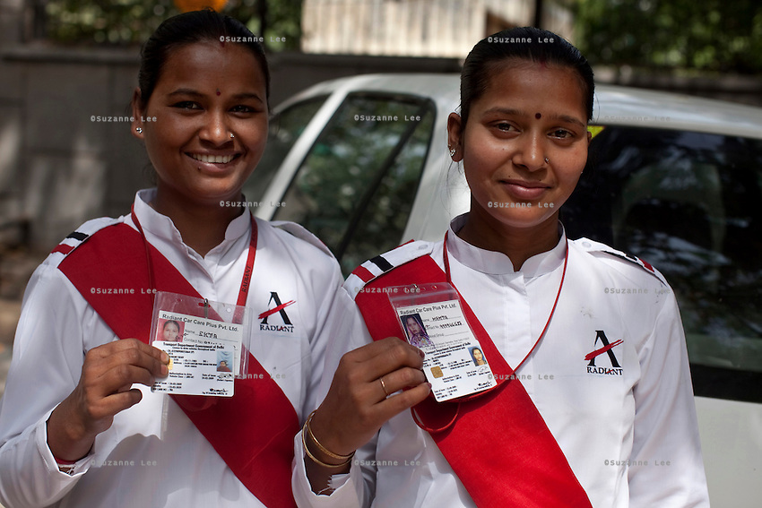 Ekta aged 28 (leftt) and Mamta (right) aged 26 pose for a photo on 30th March 2010 with their driving licences and chaffeur cards.<br /> These female drivers were part of a program by Azad Foundation.<br /> Currently training their 4th batch of students, Azad Foundation was set up by Meenu Vadera (Executive Director) in New Delhi, India, to train Indian women in driving services. Upon completion, these women work as personal drivers for a period of time before they upgrade their driving licences to commercial licences, allowing them to drive taxis. With this program, Azad aims to empower Indian women including those previously abused or trafficked, while making Delhi a safer place for women travelling in public transport. Photo by Suzanne Lee for Panos London