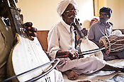 75-year-old Manganiyar artist, Saqar Khan (centre) sings and plays Kamancha (music instrument) while his two sons, Ghewar Khan (45, Left on Kamancha) and Firoze Khan (38, right on Dholak) accompany him during field recordings inside their house in Hamira village of Jaiselmer district in Rajasthan, India. Photo: Sanjit Das/Panos