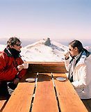 ARGENTINA, Bariloche, Cerro Cathedral, happy couple drinking coffee in winter with snow capped mountain in the background