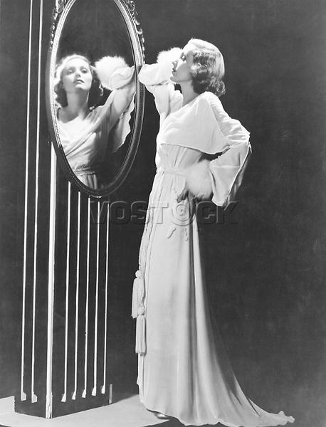 Glamorous woman looking in mirror