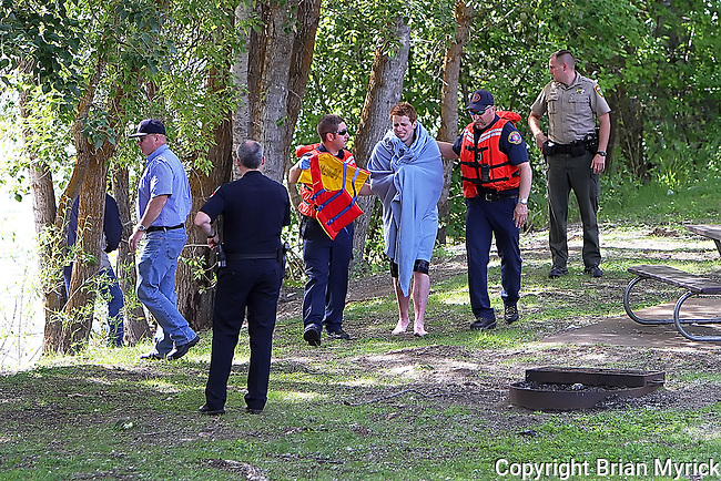 A victim of a river rafting accident is walked to a nearby ambulance at the Irene Rinehart boat launch after being rescued by members of the Kittitas County Sheriff's Office swiftwater rescue team, Friday, Jun 15, 2012. (Brian Myrick / Daily Record)