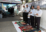 Palestinians pray in the Red Cross yard during the Friday prayer in East Jerusalem , Friday 23 July 2010, in solidarity with PLC members and former Palestinian minister Ahmad Atwon, Mohammad Totah and Khalid Abu Arfeh. After the Israeli authorities have threatened them with expulsion from Jerusalem because of their affiliation to Hamas, and after arresting their colleague Mohammed Abu Tair, the three had moved into the grounds of the International Red Cross in East Jerusalem in protest at the deportation orders. Photo by Mahfouz Abu Turk
