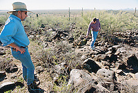 At (left), Stephen  Ross, an archaeologist for the Arizona State Land Department and John Madsen, (right), associate curator for the Arizona State Museum (621-4795) shows a spot vandals have dug up a large volcanic rock bearing rock art and removed it from the prehistoric site. Later he took us to a historic site to show how a bulldozer from the La Oso Ranch earthmoving went off course and crossed onto BLM land and cut across a historical archaeological site...