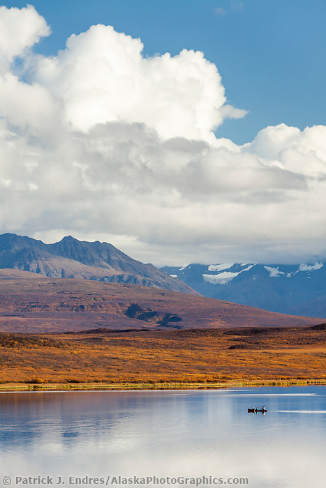 Canoers paddle on a calm lake in the Alaska Range mountains, along the Denali highway, Interior, Alaska.