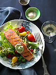 A grilled fillet of salmon on a green salad with cherry tomatoes and avocado sour cream