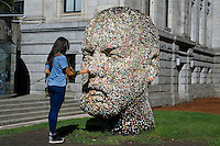Young woman placing chewing gum on Gumhead sculpture by Douglas Coupland outside the Vancouver Art Gallery, Vancouver, BC, Canada