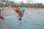 """A man jumps off the Wall at Waikiki. The """"Wall"""" at Waikiki is a favorite place for tourists and locals to hang-out to see the sunrise, sunsets, swim, surf or just to to meet friends."""
