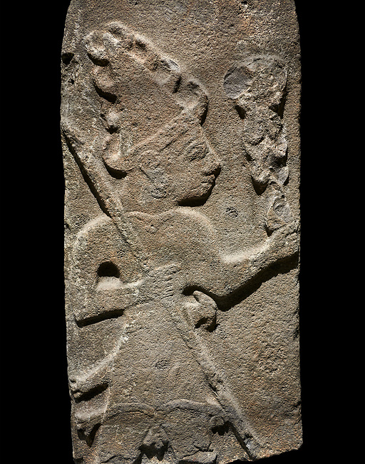 Hittite monumental relief sculpture ofa God probably holding lightning rods. Late Hittite Period - 900-700 BC. Adana Archaeology Museum, Turkey. Against a black background