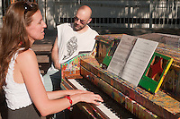 "New York, NY 21 June 2010 - Performing artist Cheryl Engelhardt plays a piano in Little Red Square...""Play Me I'm Yours"" is a musical installation by British artist Luke Jerram who has been touring the project globally since 2008. From 9am-10pm each day, 60 pianos will be available to play across New York City. Presented by Sing for Hope they are located in public parks, streets and plazas the pianos will be available until 5th July for any member of the public to play and engage with."