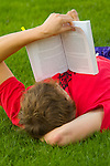 Young college student laying on the grass, reading a book