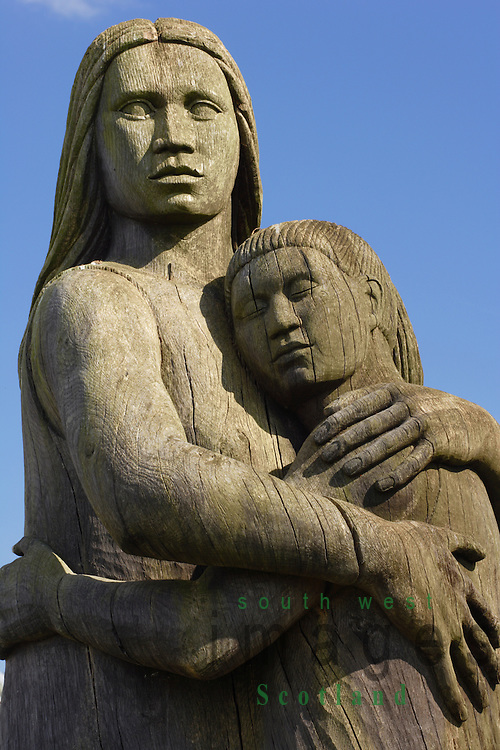 Wood sculpture of mother and child a monument to loved ones lost at sea near Kirkcudbright harbour Galloway Scotland UK