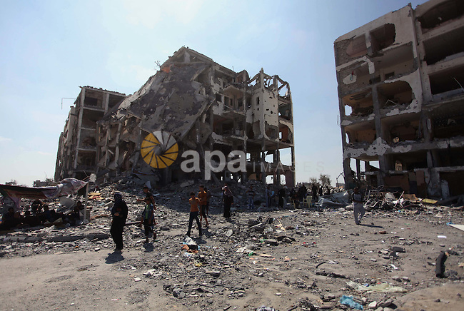 A picture taken on August 11, 2014 in Beit Lahia in the northern Gaza Strip shows the destroyed Nada Towers as Palestinians return to the area to inspect what remains of their homes during a 72-hour ceasefire observed in the Gaza Strip. Almost 12 hours into the truce, the skies over Gaza remained calm, with no reports of violations on any side and signs of life emerging on the streets of the war-torn coastal enclave which is home to 1.8 million Palestinians. Photo by Ashraf Amra