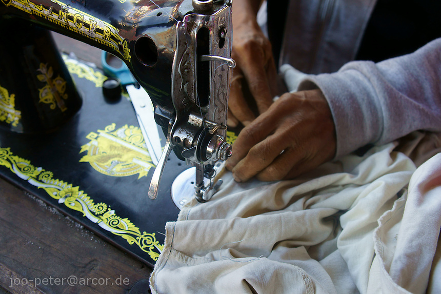 tailor on the market in Moni, working with old mechanical singer sewing machine, island  Flores in archipelago of Indonesia