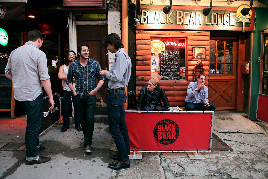 Big Buck players including Alex DerHohannesian, in plaid, step outside of The Black Bear Lodge in Manhattan for a smoke. The bar hosted an official Big Buck Party on Thursday April, 28, 2011. Fans of the popular hunting arcade game were invited to test their skill against other Big Buck Hunter fans to compete for prizes, enter to win raffle merchandise and meet Big Buck Girls...Danny Ghitis for The New York Times