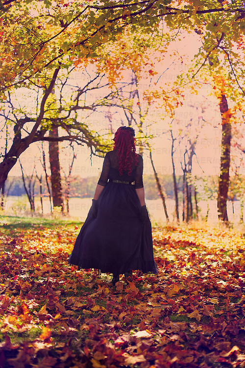 A redheaded woman in a fancy dress, walking away in some beautiful autumn woods