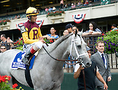 Awesome Maria and John Velazquez make their way down victory lane at Belmont Park after the Ogden Phipps, accompanied by Jonathan Thomas, assistant to trainer Todd Pletcher.