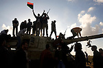 People celebrate on top of a destroyed tank, in Benghazi, Libya, March 20, 2011. Supported by a United Nations Security Council Resolution, France, Great Britain and the United States began a military campaign March 19 against the forces of Col. Muammar Qaddafi, imposing a no-flight zone in Libya. Early on March 20, the military action expanded to cripple Qaddafi's ground forces, leaving dozens of destroyed military vehicles along the road east to Benghazi.