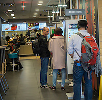 """Diners order at """"Create Your Taste"""" kiosks at a McDonald's in New York on Tuesday, April 26, 2016. The interactive iPad-like digital displays allow customers to customize their order with toppings, new sauces, etc. The McDonald's Corp. recently reported a 35% increase in profits directly attributed to their """"Breakfast All Day"""" promotion. . (© Richard B. Levine)"""