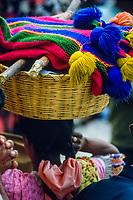 Guatemala, mercato di Chichicastenango. Donna con cesta di sciarpe colorate sulla testa.<br /> Guatemala, Chichicastenango market. Woman with basket of colorful scarves on her head.