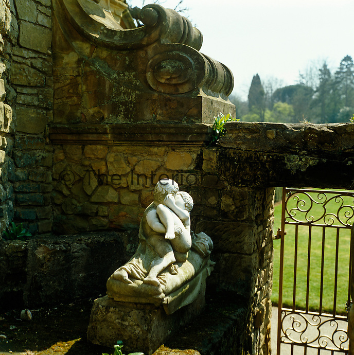 A marble statue of an amorous couple hidden behind a wall in the Italian garden at Hever Castle