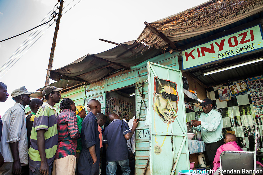 "Men gather to watch poll results on a televison inside Super Cutz Kinyozi, a barber shop in Kikuyu, Kenya, a stronghold of Presidential candidate Uhuru Kenyatta in the 2013 Kenyan national elections. The spectators expected a victory for Kenyatta- "" we will dance until midnight, the drums and trupets are redady to celebrate our president,"" one spectator said. march 8, 2013, Kikuyu, Kenya. Brendan Bannon/Polaris"