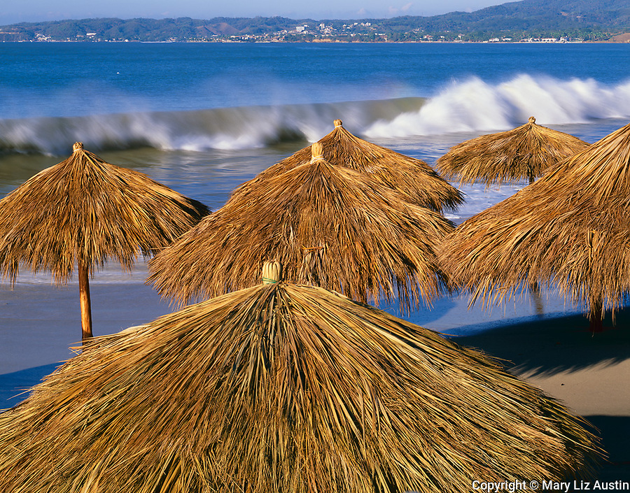 Nayarit, Mexico:  Thatched paraguas on the beach in the village of Bucerias with Bahia de Banderas (Banderas Bay) and Punta de Mita in the distance