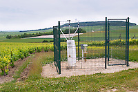 A meteorological station measuring weather conditions with a fence around it in the vineyard at the experimental vineyard of the CIVC at Plumecoq near Chouilly in the Cote des Blancs It is used for testing clones soil treatment vine treatments spraying, Champagne, Marne, Ardennes, France