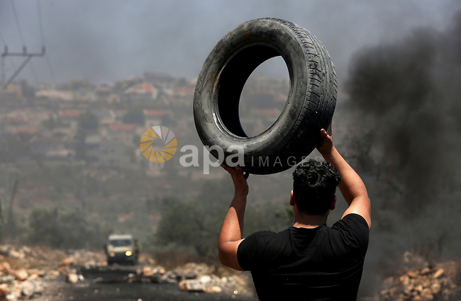 A Palestinian protester carries a tire during clashes with Israeli security forces following a weekly demonstration against the expropriation of Palestinian land by Israel in the village of Kfar Qaddum, near Nablus, in the occupied West Bank on June 30, 2017. Photo by Ayman Ameen
