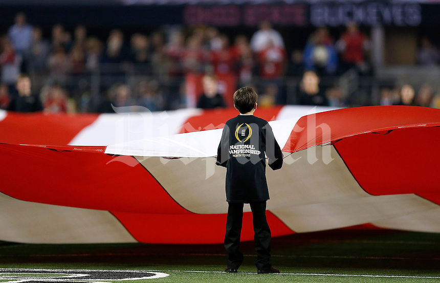 The flag is unfurled before the College Football Playoff National Championship at AT&T Stadium in Arlington, TX on Monday, January 12, 2015. (Columbus Dispatch photo by Jonathan Quilter)