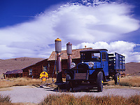 Fine art western landscape of blue 1927 Dodge truck with yellow hub caps next to antique Shell gas station and 1800's wooden structure at ghost town Bodie, Northern California, eastern side of the Sierras, with a bold blue summer sky and dramatic contrasting white clouds.